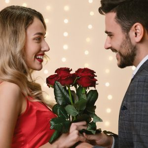 Valentine's Day Flowers. Loving Man Giving Roses To His Happy Girlfriend